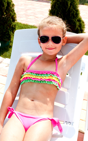 Smiling little girl lying on a chaise lounge and sunbathing