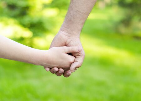 Photo pour Child holding father hand outdoor. Care trust and helping concept - image libre de droit