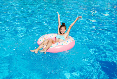 Photo pour Cute smiling little girl in swimming pool with rubber ring. Child having fun on vacation in summertime - image libre de droit