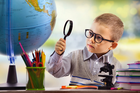 Boy looking through magnifying glass at globe, isolated on white background. School, education concept.