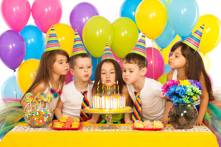 Photo for Group of joyful little kids celebrating birthday party and blowing candles on cake. Holidays concept. - Royalty Free Image