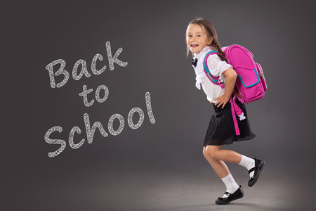 Little girl with a backpack going to school. Place for text, education background. School, fashion concept