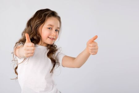 Photo pour Little girl showing thumbs up gesture isolated on white background. - image libre de droit