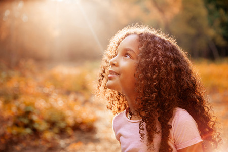 Photo pour Afro american cute little girl with curly hair receives miracle sun rays from the sky - image libre de droit