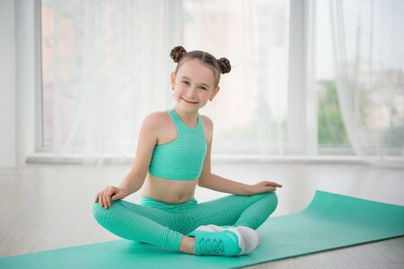 Photo pour Little sporty girl gymnast in sportswear doing exercises on a mat indoor - image libre de droit