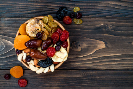 Photo pour Mix of dried fruits and nuts on a dark wood background with copy space. Top view. Symbols of judaic holiday Tu Bishvat - image libre de droit