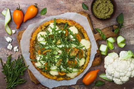 Photo pour Cauliflower pizza crust with pesto, yellow tomatoes, zucchini, mozzarella cheese and squash blossom. - image libre de droit