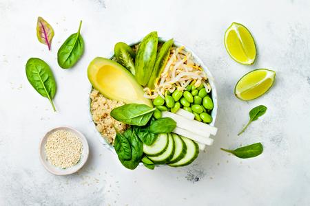 Foto de Vegan, detox green Buddha bowl recipe with quinoa, avocado, cucumber, spinach, tomatoes, mung bean sprouts, edamame beans, daikon radish. Top view, flat lay - Imagen libre de derechos
