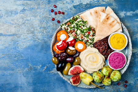 Photo pour Middle Eastern meze platter with green falafel, pita, sun dried tomatoes, pumpkin and beet hummus, olives, stuffed peppers, tabbouleh, figs. Mediterranean appetizer party idea - image libre de droit