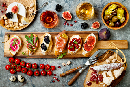 Photo pour Appetizers table with italian antipasti snacks and wine in glasses. Brushetta or authentic traditional spanish tapas set, cheese variety board over grey concrete background. Top view, flat lay - image libre de droit