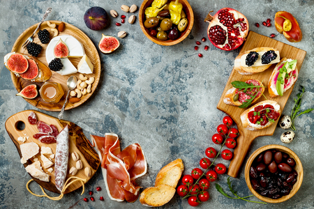 Appetizers table with italian antipasti snacks. Brushetta or authentic traditional spanish tapas set, cheese variety board over grey concrete background. Top view, flat lay, copy space
