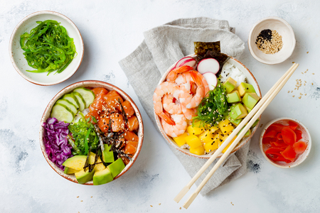 Foto de Hawaiian salmon and shrimp poke bowls with seaweed, avocado, mango, pickled ginger, sesame seeds. Top view, overhead, flat lay - Imagen libre de derechos