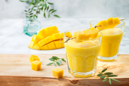 Foto de Mango Lassi, yogurt or smoothie with turmeric. Healthy probiotic Indian cold summer drink - Imagen libre de derechos