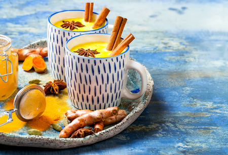 Photo for Turmeric golden milk latte with cinnamon sticks and honey. Detox, immune boosting, anti inflammatory healthy cozy drink - Royalty Free Image