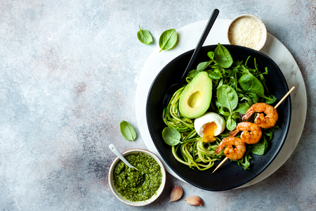 Foto de Buddha bowl with soft boiled egg, avocado, greens, zucchini noodles, grilled shrimps and pesto sauce. Vegetarian vegetable low carb lunch bowl. - Imagen libre de derechos