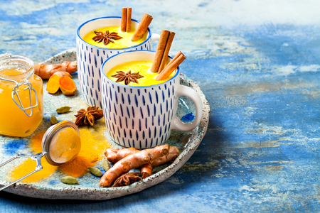 Foto de Turmeric golden milk latte with cinnamon sticks and honey. Detox, immune boosting, anti inflammatory healthy cozy drink - Imagen libre de derechos
