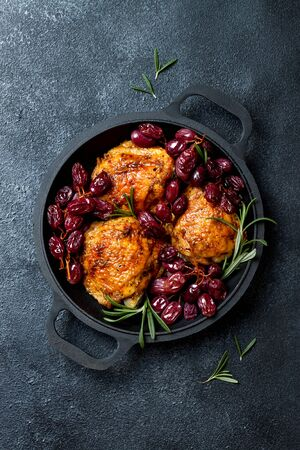 Photo for Roasted chicken legs with red grapes on pan over black slate stone - Royalty Free Image