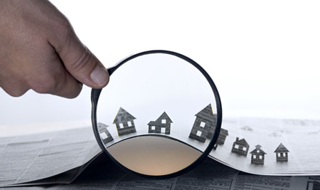Photo pour Hand holds the magnifying glass in front of an open newspaper with paper houses. That could mean rent, search, purchase real estate. - image libre de droit