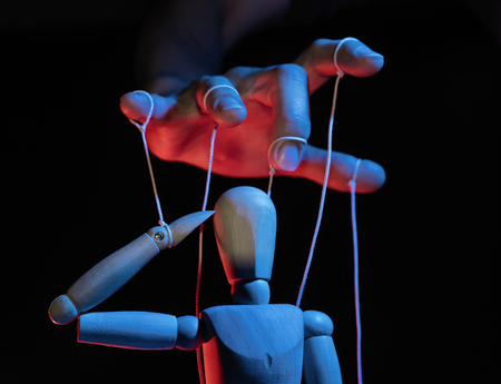 Foto de Concept of control. Marionette in human hand. Objects are colored on red and blue light. - Imagen libre de derechos
