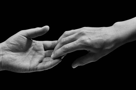 Foto de Black and white photo of two hands at the moment of breakup. The concept of  breakup. On black isolated background. Image. - Imagen libre de derechos