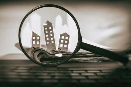Photo pour Magnifying glass in front of an open newspaper with paper houses. Concept of rent, search, purchase real estate. - image libre de droit