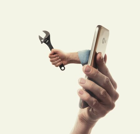 Foto de The human hand with  black wrench stick out of a smartphone screen. Concept of technical support. - Imagen libre de derechos