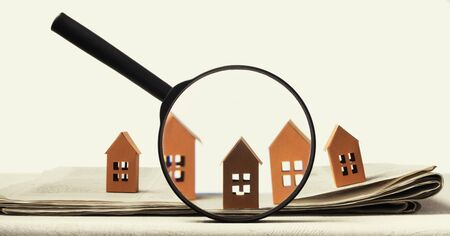 Photo pour Magnifier in front of an open newspaper with paper houses. Concept of rent, search, purchase real estate. - image libre de droit