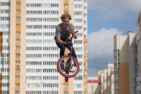 Belarus, Gomel, June 24, 2018. Central park. Extreme cycling.A dangerous trick on a bicycle against the backdrop of the city.Professional cyclist jumped high