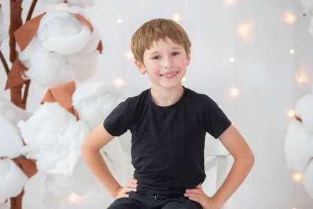 Foto de A boy in dark clothes on a bright background. Happy child smiling - Imagen libre de derechos