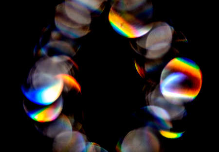 Photo pour Lens flare, Bokeh lights. Reflections from glass, diamond, crystal. Defocused shining colorful rainbow light leaks, rays on black background - image libre de droit