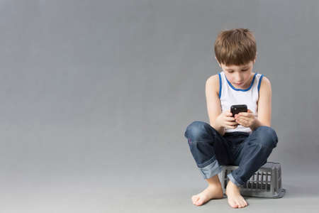 Photo pour Child with a mobile phone. Schoolboy looks into the smartphone on a gray background - image libre de droit
