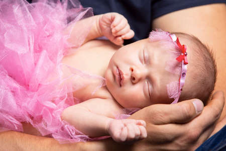 Photo pour A newborn baby sleeps in his fathers arms. Cute newborn baby girl. - image libre de droit