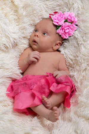 Photo pour Beautiful newborn baby girl in pink clothes on a fur bed. - image libre de droit