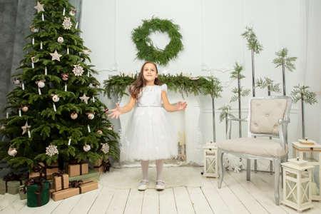 Foto de Elegant child at the Christmas tree. Little joyful girl in christmas - Imagen libre de derechos