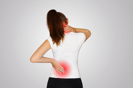 Photo pour Pain in the neck and back. A young woman suffers from pain in the neck and back. Spine osteoporosis. Scoliosis. The place of pain indicated by a red spot. Concept of health. - image libre de droit
