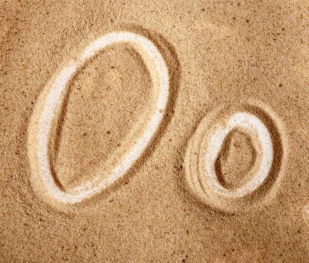 Photo pour Letter O. English Handwritten Alphabet In The Sand. - image libre de droit