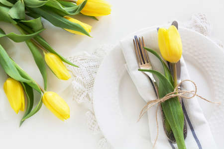 Photo pour Easter concept with copy space for your Happy Easter wishes. Decorative easter place setting with yellow tulip, a quail egg on a white background. - image libre de droit