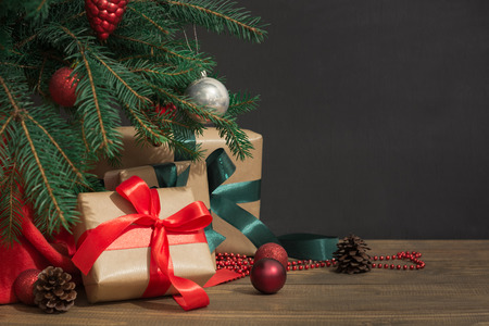 Foto de Christmas holiday background. Gifts with a red ribbon, Santa's hat and decor under a Christmas tree on a wooden board. Close up. Copy space on chalkboard. - Imagen libre de derechos