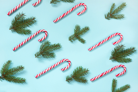 Christmas candy cane lied evenly in row on blue background. Flat lay and top view. Pattern.