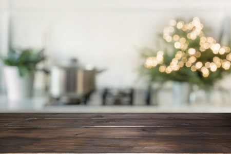 Photo pour Empty wooden tabletop for display products and blurred kitchen with Christmas tree as background. - image libre de droit