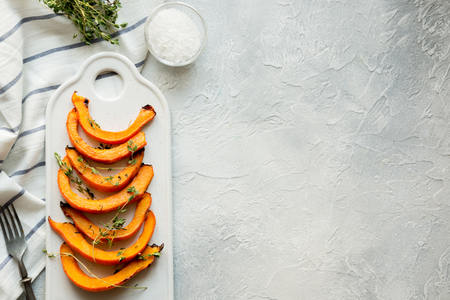 Photo for Roasted, grilled pumpkin with addition aromatic thyme and salt on white. Healthy vegan food. View rom above. - Royalty Free Image