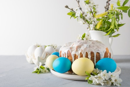 Photo for Easter cake, colored eggs on the event family table with cherry blossoms flowers as decor. Space for text. - Royalty Free Image