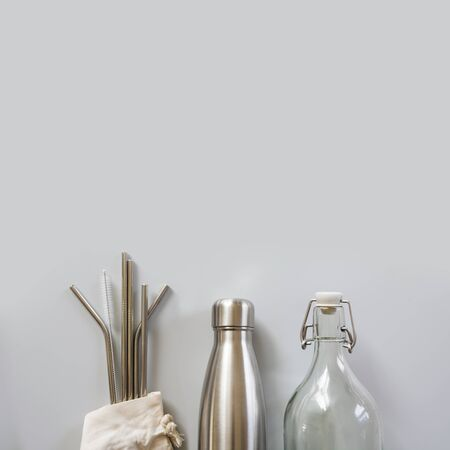 Photo for Eco natural metallic straws, bottle with cotton bag on grey. Sustainable lifestyle concept. Zero waste, plastic free. Pollution environment. - Royalty Free Image