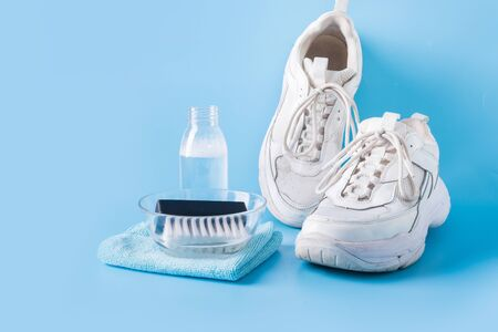 Foto de Dirty white sneakers with brush and special tool for cleaning them on blue background. Washing concept. Regular care about sneakers. Space for text. - Imagen libre de derechos