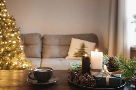 Photo pour Cozy interior with Christmas tree and warm cup of coffee on wooden tabletop with candles, gifts cones in living room. Xmas holiday at home. - image libre de droit