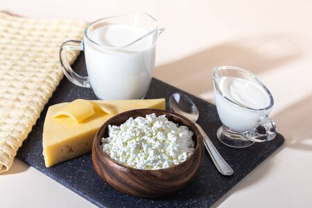 Photo pour Food is a source of calcium, magnesium, protein, fats, carbohydrates, balanced diet. Dairy products on the table: cottage cheese, sour cream, milk, cheese, contain casein, albumin, globulin, free lactose - image libre de droit