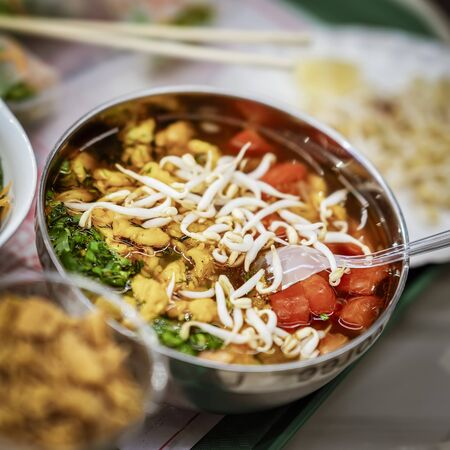 Photo pour Asian food, spicy soup with vegetables, seafood and germinated soybean sprouts in a bowl close-up, top view. Selective focus - image libre de droit