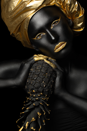 Photo pour black woman with black pineapple in her hands, gorgeous image of black and zloty - image libre de droit