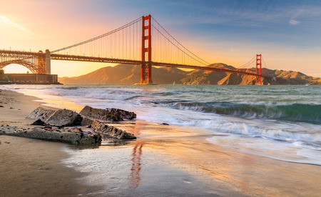 Foto de Long exposure of a stunning sunset at the beach by the famous Golden Gate Bridge in San Francisco, California - Imagen libre de derechos