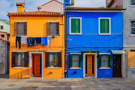 Bright and colorful picturesque houses with fresh laundry hanging outside n Burano island near Venice Italy, known for lace making. in Burano island near Venice Italy, which is known for lace making.